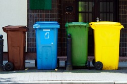 Four colored containers for segregated rubbish. The bins are standing on the street waiting for the garbage truck. Poland, Warsaw.