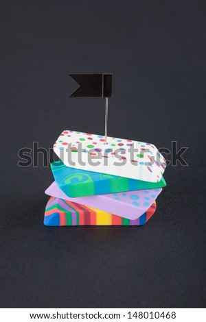 Four colored eraser with black flag on the black background