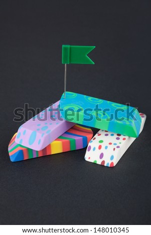 Four colored eraser with green flag on the black background