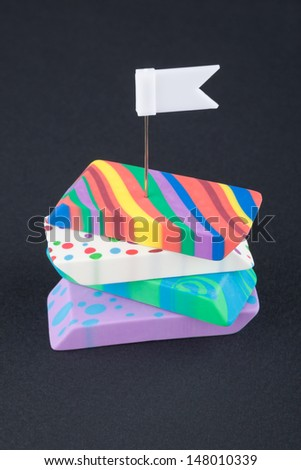 Four colored eraser with white flag on the black background