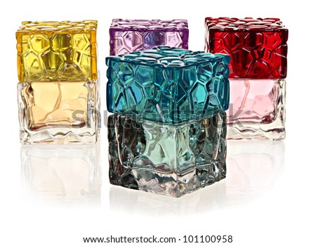four colored glass bottles of perfume on a white background with the reflection.