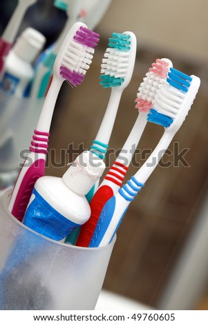 Four colored tooth-brushes in a glass