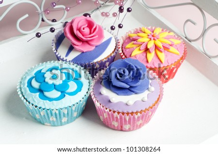 four colorful cupcake with flowers