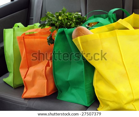 Four colorful eco-friendly shopping bags filled mostly with groceries in the back seat of a car.
