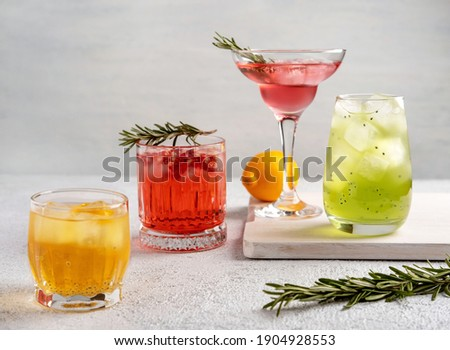 Four colorful summer cocktails in glasses on  white table. Assortment of fresh  summer drinks. Pink and red sangria cocktails, orange punch cocktail, margarita cocktail, tropical mule.