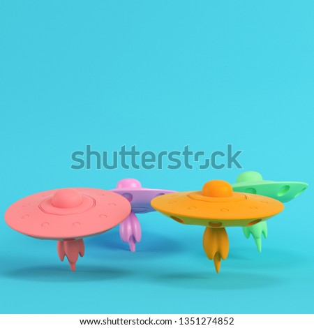 Four colorful ufos or alien spaceships on bright blue background in pastel colors. Minimalism concept. 3d render