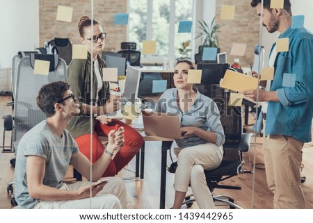 Four coworkers communicating together in meeting room. Stickers are on glass #1439442965