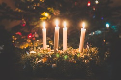 four cristian candles, one pink and three purple burning on christmas tree background