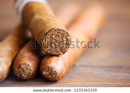 Four cuban cigars on wooden table close up
