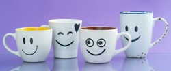 Four cups with funny faces on a color background. The concept of a friendly company, a big family, meeting friends for a cup of tea or coffee. Smiles on white coffee mug