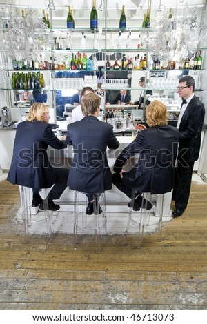 four customers and a barkeeper sitting, standing, talking and drinking at a bar