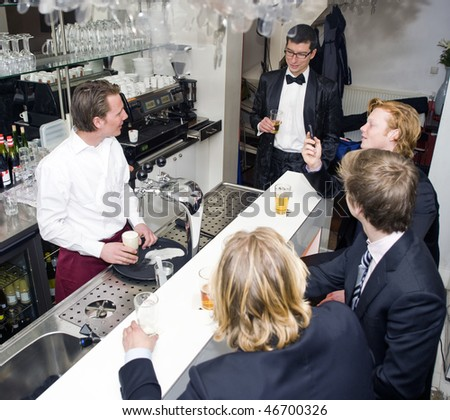 Four customers around a bar, being served by a barman