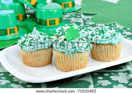 Four decorated cupcakes in a festive St. Patrick's day setting with shamrocks and fedoras.
