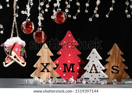 Four decorative wooden Christmas trees with carved letters xmas on black background. Xmas family traditions.