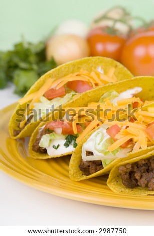 Four delicious tacos on a plate. Fresh ingredients in the background. Selective focus on the front taco.