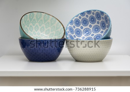 Four designer ceramic bowls in different colors stacked together. Bowls on white background in restaurant cafe. Blue, turquoise, grey and dark blue bowls.