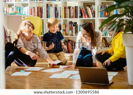Four different age smiling children sitting together on floor in labrary. Team of pupils collaborating in school researching and planning strategy for future project. sun glare effect. #1300695586