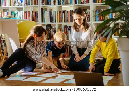 Four different age smiling children sitting together on floor in labrary. Team of pupils collaborating in school researching and planning strategy for future project. sun glare effect. #1300695592