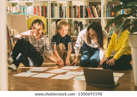 Four different age smiling children sitting together on floor in labrary. Team of pupils collaborating in school researching and planning strategy for future project. sun glare effect. #1300695598