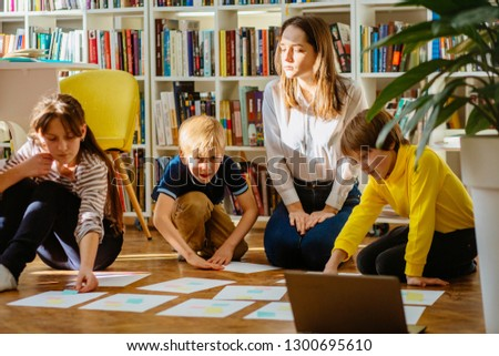 Four different age smiling children sitting together on floor in labrary. Team of pupils collaborating in school researching and planning strategy for future project. sun glare effect. #1300695610