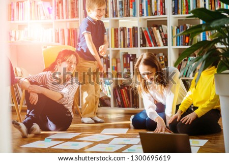 Four different age smiling children sitting together on floor in labrary. Team of pupils collaborating in school researching and planning strategy for future project. sun glare effect. #1300695619