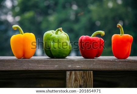 Four different colored peppers on a wood ledge