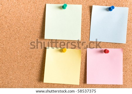 four different colour notes on cork board, each attached by color matched pin, green, blue, yellow, pink - stock photo