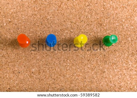 four different colour pins on corkboard, red, blue, yellow and green