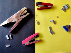 Four different sized staplers and stapler pins isolated on yellow background. Top view
