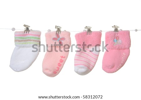 Four different socks for baby girl hanging on rope, isolated.