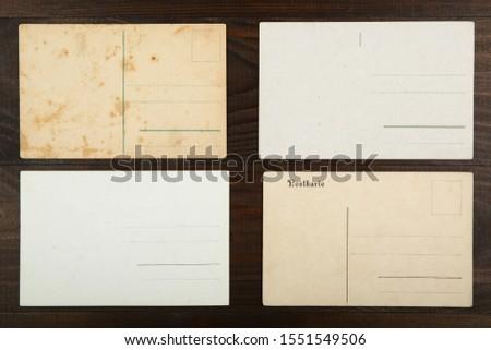 "four different vintage postcards on wooden background. translation from German ""postcard"" #1551549506"
