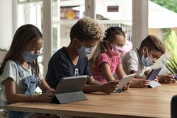 Four diverse kids wear facemasks sit at table use wireless gadgets ignoring each other prefer internet games and virtual communication. Alpha generation and modern technology overuse, phubbing concept
