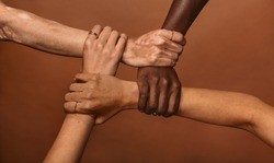 Four diverse women holding each others wrists in a circle. Top view of female hands linked in the lock against brown background.