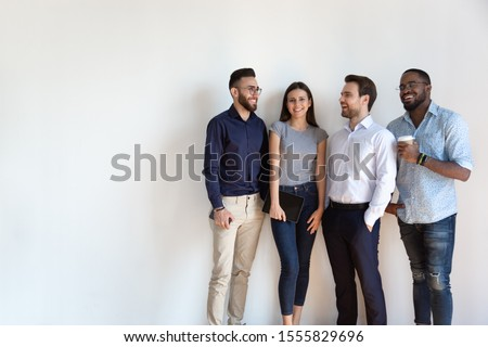 Four diverse young business people pose near grey white wall studio background copy space for ad text, millennial generation arab african european professionals, human resources, new workforce concept