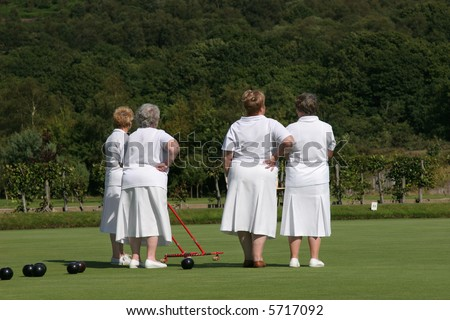 Four elderly females (rear view) dressed  in white lawn bowling outfits and standing on a bowling green. One of the ladies is holding a red metal ball gatherer. Trees and shrubs to the rear.