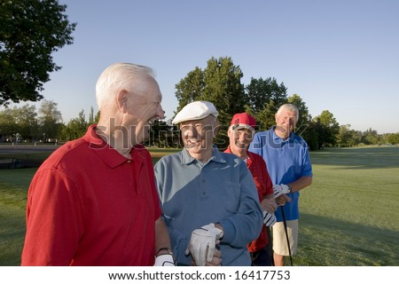 Four elderly men are standing together on a golf course. They are holding their clubs, smiling, and looking at each other.  Horizontally framed shot.