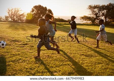 Four elementary school kids playing football in a field - Shutterstock ID 667949983