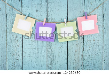 Four empty colorful photo frames or notes paper hanging with clothespins on wooden blue vintage shabby chic background