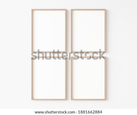 Four empty vertically oriented rectangular picture frames with thin wooden border hanging matrix-arranged on white wall. 3D illustration.