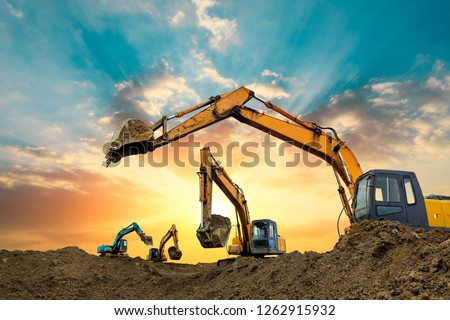 Four excavators work on construction site at sunset