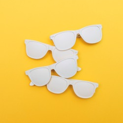 four fashion sunglasses for hipsters painted white on a yellow background. flat lay minimalism.