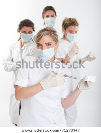 Four female dentists posing with masks and equipment