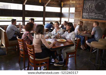 Four female friends at lunch in busy restaurant, full length