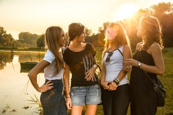 Four female friends standing near river bank and looking at camera at sunset.