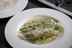 Four filets of Dover sole arranged on a plate with beurre blanc and chives
