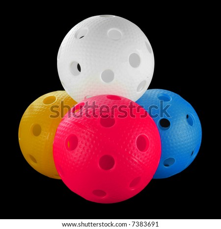 Four floorball balls isolated on a black background (white, blue, orange and pink)