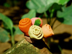 Four flower group with green leaf on center created with soft clay colorful soil material at natural park background.