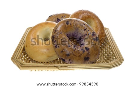 Four fresh assorted bagels with plain, whole grain and blueberry in a wicker basket on a white background.