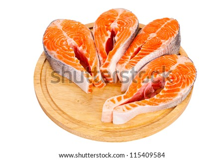 Four fresh raw salmon steaks are laying  on the cutting board