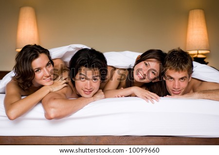 Four friends all lying together in a double bed